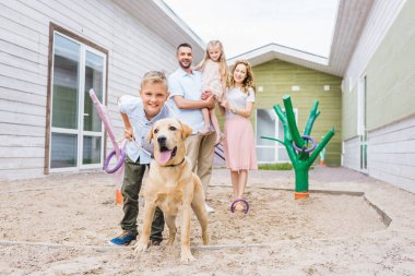 parents and children standing with adopted labrador at animals shelter