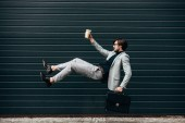 side view of young businessman falling with paper cup of coffee in front of roller gate