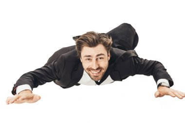 close-up shot of smiling young businessman falling and looking at camera isolated on white