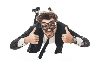 smiling young businessman in vintage aviation goggles falling and showing thumbs up isolated on white