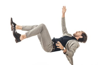 frightened young businessman in suit falling isolated on white