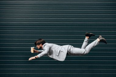 side view of handsome young businessman falling with paper cup of coffee in front of roller gate