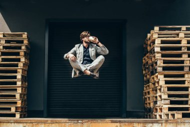 handsome young businessman floating in air in lotus pose and drinking coffee at industrial location in front of roller gate