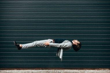 side view of young businessman lying on back in air in front of roller gate