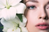 Fotografie partial view portrait of beautiful young woman with white lilium flowers