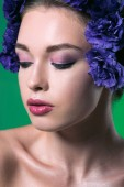 Fotografie close-up portrait of beautiful young woman with eustoma flowers on head and closed eyes isolated on green