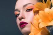 Fotografie Detailní portrét atraktivní mladá žena s módní make-up a květy oranžové lilium při pohledu na fotoaparát izolované Grey