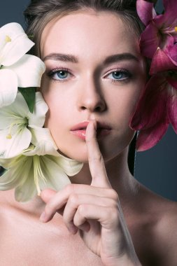 close-up portrait of beautiful young woman surrounded with lilium flowers showing silence gesture