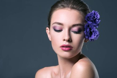 beautiful young woman with eustoma flowers in hair and closed eyes isolated on grey