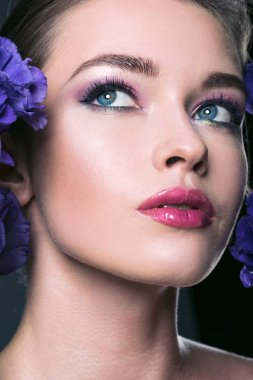 close-up portrait of beautiful young woman with fashionable makeup and eustoma flowers
