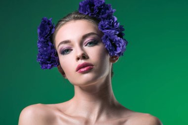 close-up portrait of attractive young woman with eustoma flowers on head looking at camera isolated on green