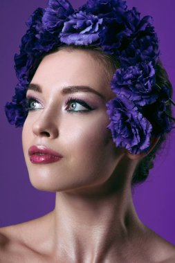 close-up portrait of beautiful young woman with eustoma flowers wreath on head looking away isolated on purple