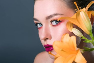 close-up portrait of stylish young woman with fashionable makeup and orange lilium flowers looking at camera isolated on grey