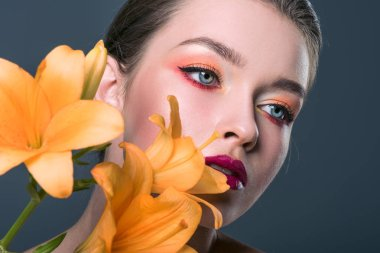 close-up portrait of attractive young woman with fashionable makeup and orange lilium flowers looking away isolated on grey