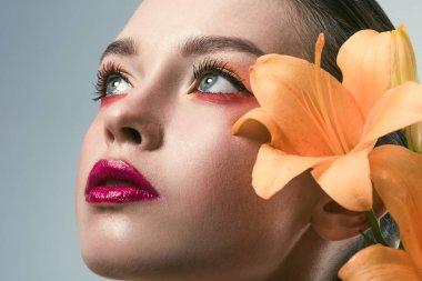 close-up portrait of beautiful young woman with stylish makeup and orange lilium flowers looking up isolated on grey