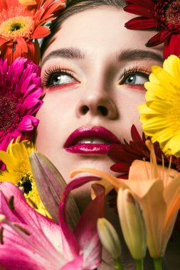 close-up portrait of attractive young woman surrounded with various flowers looking up