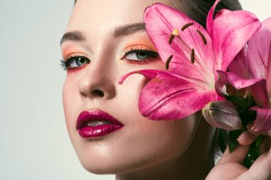 close-up portrait of beautiful young woman with stylish makeup and pink lilium flowers isolated on white