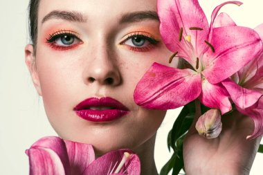 close-up portrait of beautiful young woman with pink lillies isolated on white
