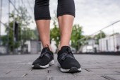Photo cropped image of sportswoman legs in black sneakers standing at street