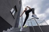 nízký úhel pohledu Asijská sportovkyně skákání ze schodů na městské ulici