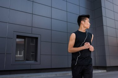 young asian sportsman in earphones running at urban street
