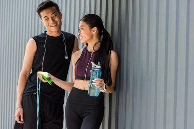 smiling asian sportswoman holding bottle of water and giving jump rope to young sportsman at street