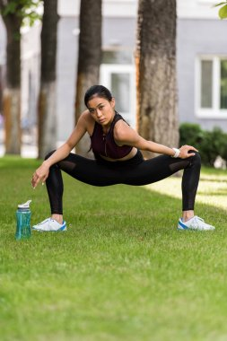 selective focus of asian female athlete stretching near sport bottle of water on grass in park