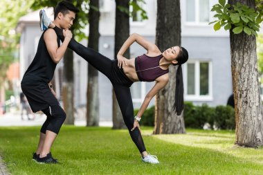 serious asian sportsman helping female athlete to stretch on grass in park