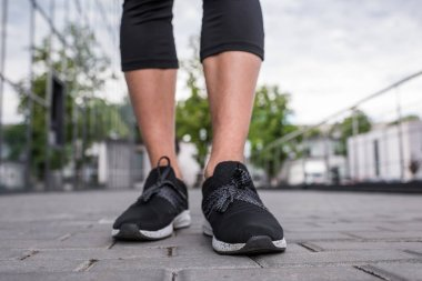cropped image of sportswoman legs in black sneakers standing at street