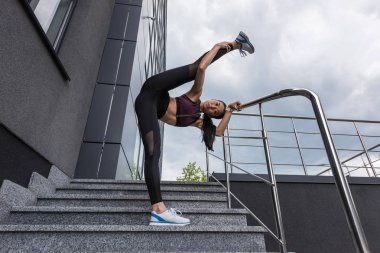 young asian sportswoman stretching on stairs at urban street