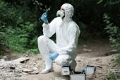 Fotografie cílené mužské vědec v ochranný oblek a maska zkoumání stone zatímco drží pomocí pinzety v lese