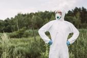 magabiztos férfi tudós védő maszk, googles és suit állt az a derék-Réti hands
