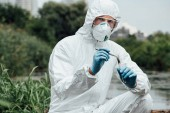 Photo serious male scientist in protective suit and mask putting sample of soil by tweezers in test flask outdoors
