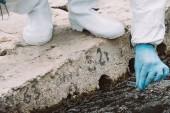 oříznutý obraz mužské vědce v latexové rukavice s vzorku vody v testu baňky venku