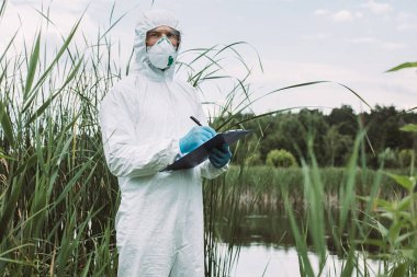 serious male scientist in protective mask and suit writing in clipboard near water outdoors
