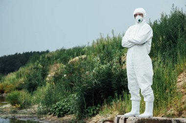 male scientist in protective suit and mask standing near water outdoors