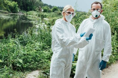 female and male scientists in protective masks and suits working with digital tablet and looking at camera outdoors