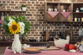 Fotografie cooking table with flowers bouquet and various products at loft style kitchen
