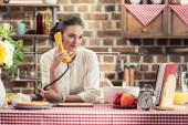 mosolygós felnőtt háziasszony retro vezetékes telefonon beszélt, és nézett konyha