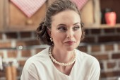 Fotografie close-up portrait of smiling adult woman in stylish vintage clothes and pearl necklace looking away