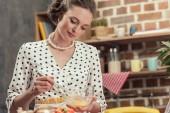 Fotografia casalinga felice adulta, montare le uova per la frittata in cucina