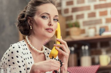 serious adult housewife talking by vintage wired phone and looking at camera at kitchen