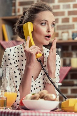 shocked adult housewife talking by vintage wired phone at kitchen
