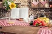 Fotografie různé výrobky tepelně neopracované a kuchařku na stůl v kuchyni vaření