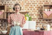 Fotografie schöne Erwachsene Hausfrau hält Schüssel mit Teig und Blick in die Kamera in Küche