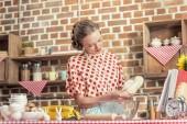 Fotografie schöne Erwachsene Hausfrau mit Teig zum Backen in Küche
