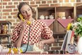 attraktive Erwachsene Hausfrau am Telefon reden und kneten von Teig in Küche