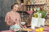 beautiful adult housewife with knife cooking and looking at camera at kitchen