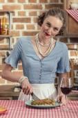 Fotografie glückliche Erwachsene Hausfrau frischen Pilz Kuchen schneiden und Blick in die Kamera in Küche