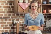 vonzó felnőtt háziasszony és frissen sült pogácsa látszó-on fényképezőgép, konyha